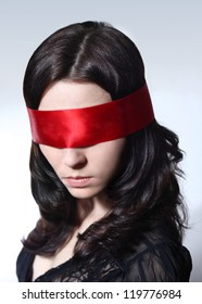 Portrait of a young Caucasian female with brown hair and red blind-folder over her eyes