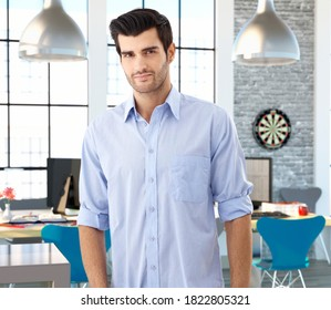 Portrait of young caucasian male officeworker at creative office space.