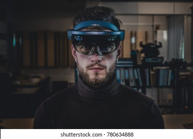 Portrait of young Caucasian male using augmented reality holographic hololens in modern office