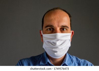 portrait of a young caucasian man wearing a protective face mask in front of a gray background. Studio shot with natural light. the new normal