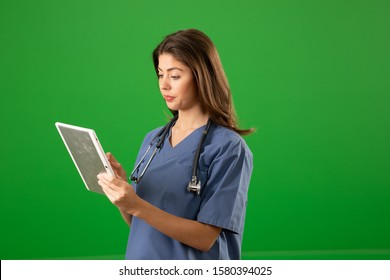 Portrait of young Caucasian medical professional using tablet on green screen. Serious woman in scrubs looking at results on digital tablet
