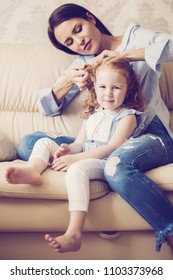 Portrait of young Caucasian mother wearing shirt and ripped jeans sitting on sofa at home and doing hair of her little redhead daughter. Little girl sitting with nanny, looking at camera and smiling