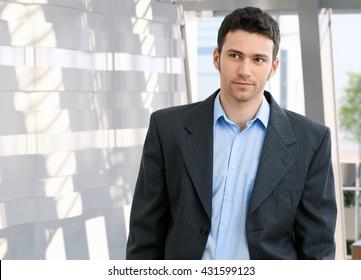 Portrait of young caucasian office worker. Suit no tie, copyspace.