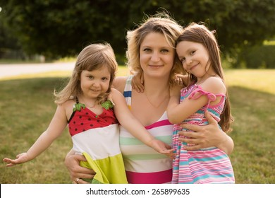 Portrait of young caucasian pregnant woman embracing with her daughters in the meadow of the park.