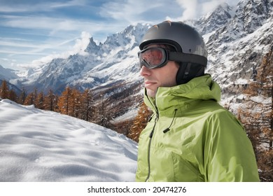 Portrait of young caucasian skier with ski goggles and helmet. on background a winter alpine landscape.