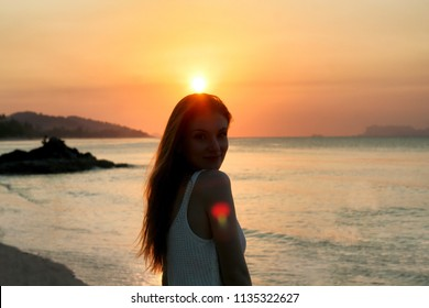 Portrait of young caucasian smiling girl besides the sea. Beautiful sunset in thailand. Concept of romantic vacation, love story.