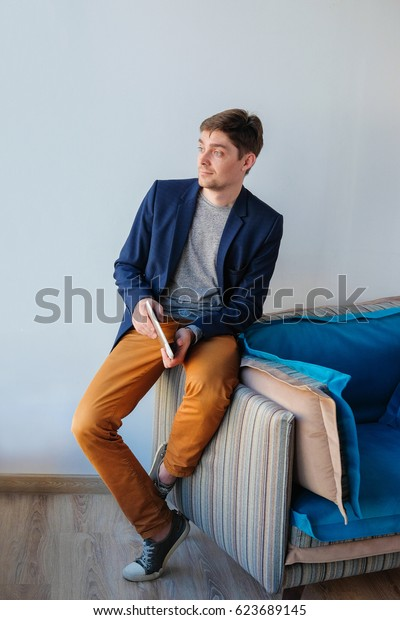 Portrait of a young Caucasian successful businessman sitting on a chair with laptop in the hands in a modern office. Handsome man with digital tablet indoors.