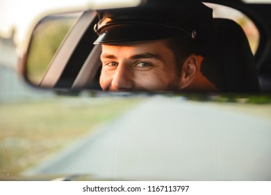 Portrait of young caucasian taxi driver man wearing uniform and cap driving car and looking in rear view mirror