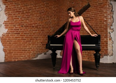 Portrait of young caucasian woman in fluffy dress standing near the grand piano.