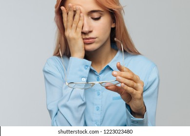 Portrait of young caucasian woman with glasses holding in hand rubbing her eyes, feels tired after working on laptop, focus on glasses. Overwork, tired concept. Exhausted and fatigue eyes