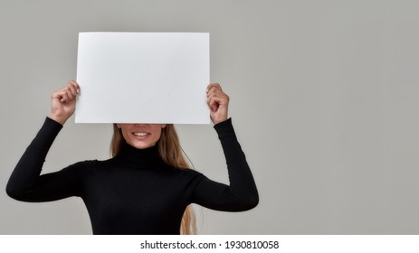 Portrait of young caucasian woman with long hair dressed in black holding white blank banner over her face, standing isolated on gray background. Advertisement concept. Copy space
