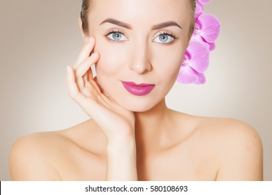 portrait of young caucasian woman with purple orchids, spa concept