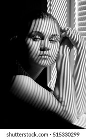 Portrait of a young Caucasian woman with shadows on her face and arms, leaning on windowsill, looking away from camera, in black and white