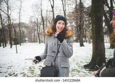 portrait of young caucasian woman standing in park with friends and using smartphone –vacation, new generation, technology