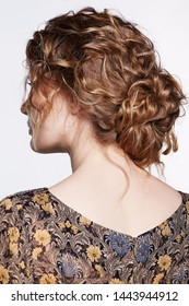Portrait of a young caucasian woman in vintage retro dress from back side. Female with wavy hair on a gray background. Girl long golden curly hair.
