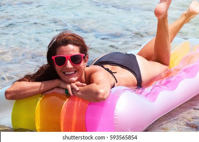 Portrait of young Caucasian woman wearing black bikini and sunglasses floating on pool raft at seaside, looking at camera and smiling. Female tourist at summer resort