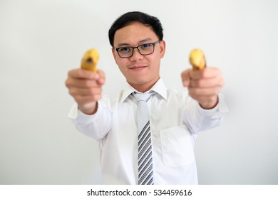 Portrait of Young CEO asian businessman uses a banana instead of a gun.