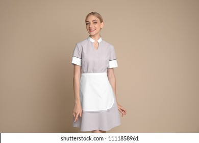 Portrait of young chambermaid in tidy uniform on color background