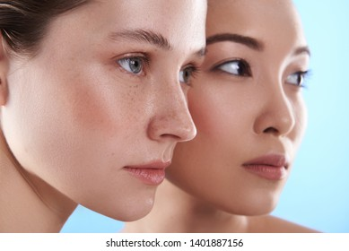 Portrait of young charming Asian and Caucasian ladies with different types of skin posing for camera in studio. They are looking away indoors. Beauty, facial treatment and spa concept. Focus on