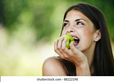 portrait young charming brunette woman biting green apple background summer park