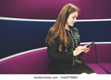 Portrait of a young charming caucasian woman entrepreneurwith a long hair sitting on the curved modern sofa of purple color in an office and using her smartphone, a copy space area on the left