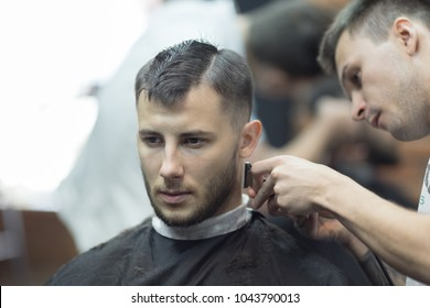 Portrait of young charming man in barbershop salon while shearing with clipper by hairdresser