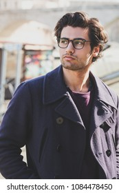 Portrait of a young and charming man outdoors. The handsome man wears a coat and eyeglasses. Trendy haircut.