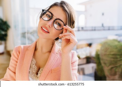 Portrait of young charming woman wearing stylish, fashionable glasses, business lady in elegant pink jacket with beige blouse, cute student with light makeup. Big window  on background.