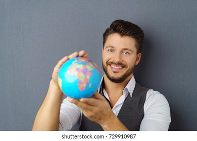 Portrait of young cheerful bearded man looking at camera holding globe against dark background