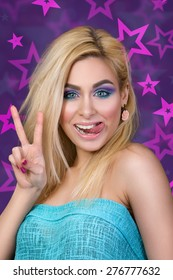 Portrait of young cheerful blonde woman showing her tongue and victory sign