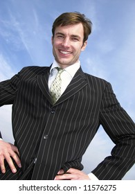 Portrait of  young cheerful businessman on  background of  blue sky