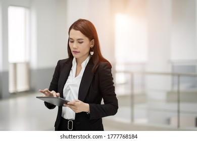 Portrait of a young cheerful businesswoman surfing social network on digital tablet in front of office during break. Asian business woman standing in office building. ฺBusiness stock photo.