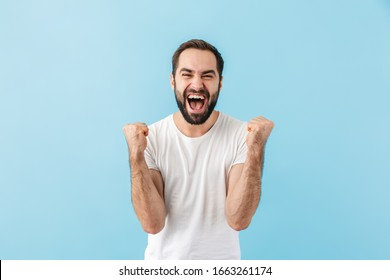 Portrait of a young cheerful excited bearded man wearing t-shirt standing isolated over blue background, celebrating success