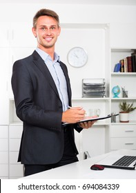 portrait of young cheerful man wearing formal wear holding clipboard in hands in office