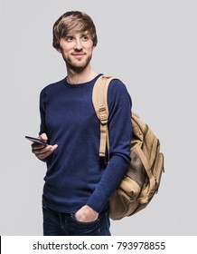 Portrait of young cheerful men with smart phone. Smiling man going on a travel. Isolated on gray background