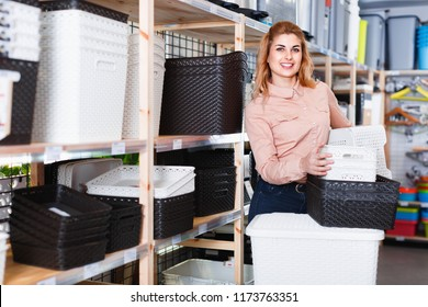 Portrait of  young cheerful positive glad woman with shopping in household store