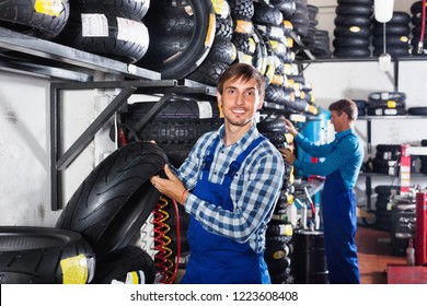 Portrait of young cheerful smiling mechanic working with bike tires in workshop