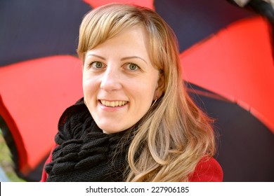 Portrait of the young cheerful woman against a black-red umbrella