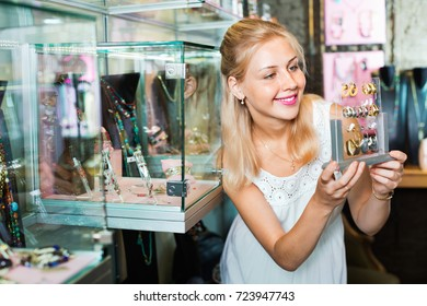 Portrait of young cheerful woman choosing earrings in shop with bijouterie
