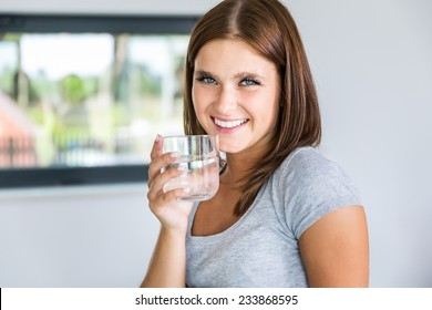 Portrait of young cheerful woman with glass of mineral water