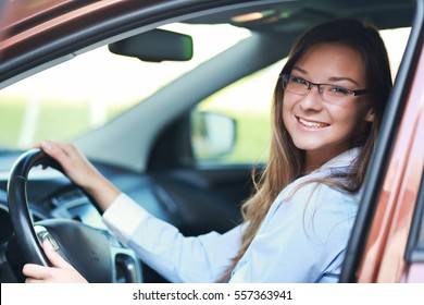 portrait of young cheerful woman in glasses sitting in the  car