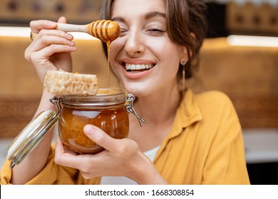 Portrait of a young and cheerful woman with a jar full of sweet honey on the kitchen at home