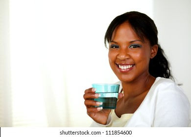 Portrait of a young cheerful woman smiling and drinking healthy cool water while looking to you. With copyspace.