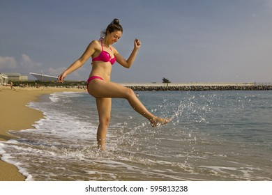 Portrait of young and cheerful woman who is splashing water with her leg. Sunny day. Barcelona, Spain