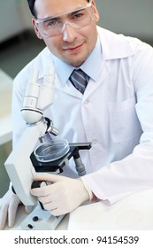 Portrait of young chemist looking at camera in laboratory