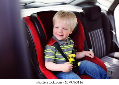 portrait of a young child of a boy with blond hair in a children's car seat. Safe transportation of children in the car.