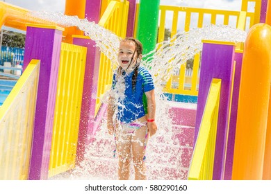 portrait of young child girl having fun in water pool