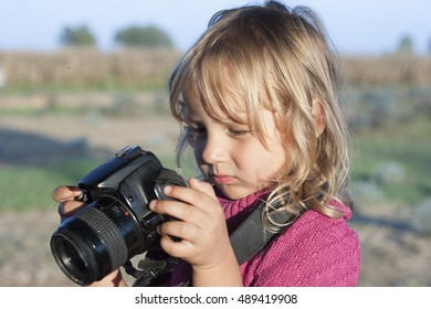 Portrait of a young child holding a photo camera
