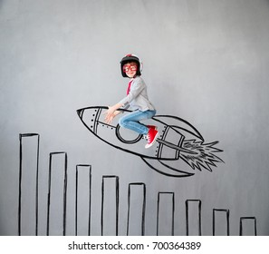 Portrait of young child pretend to be businessman. Kid playing at home. Child flying on drawn rocket over chart bar. Imagination, idea and creative concept. Copy space for your text