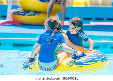 portrait of young children having fun in water pool